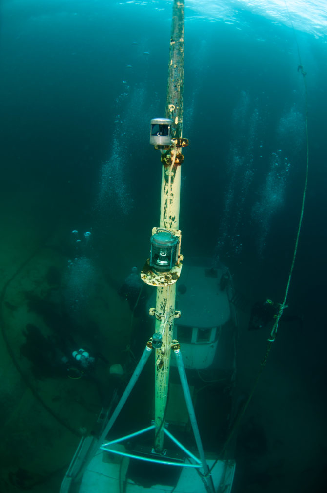 The boat mast goes almost up to the surface. Divers exploring the fresh wreck